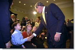 President George W. Bush talks to Solveig Haugen, her twin sister Liv and their younger brother Tad, after the signing of the Dot Kids Implementation and Efficiency Act of 2002 in the Roosevelt Room, Dec 4. The Haugen family of Loudoun County, Virginia is one family that will benefit from the act. The bill creates a second level Internet domain (kids.us), within the United States country code, that will provide a safe online environment for children ages 13 and under. White House photo by Eric Draper.